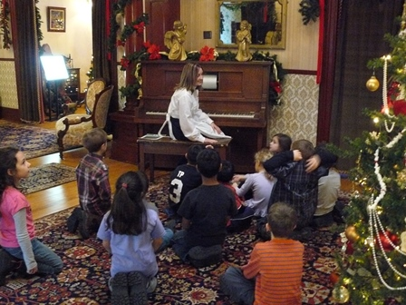 Visitor Experience Host at the player piano with a group of students sitting on the floor.