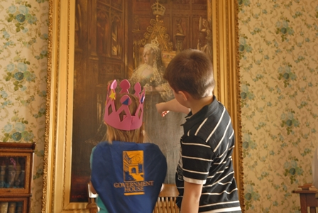 Two children point at laarge portrait of Queen Victoria in the Library of the museum