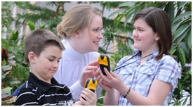 Vsitor Experience Host with two children holding GPS devices.